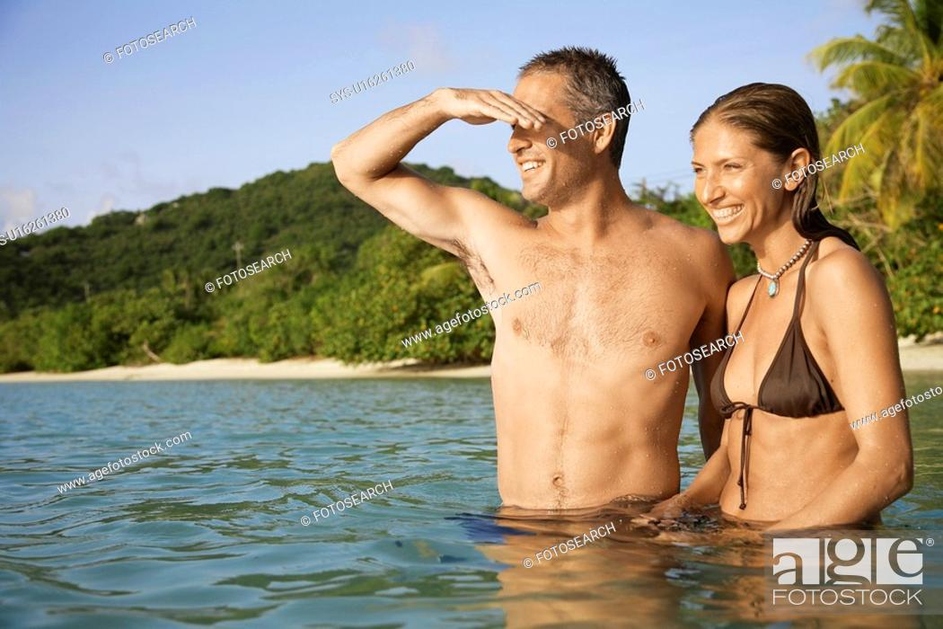 Stock Photo: Mid adult couple standing in water and looking at view, St. John, US Virgin Islands, USA.