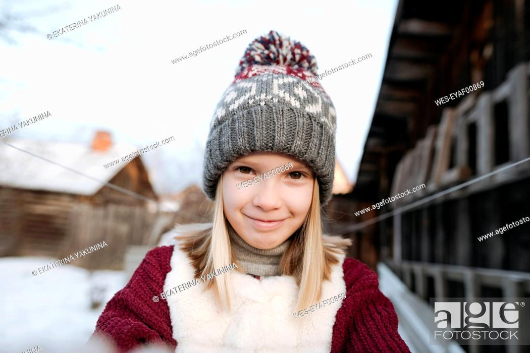 Stock Photo: Portrait of smiling girl wearing woolly hat in winter.