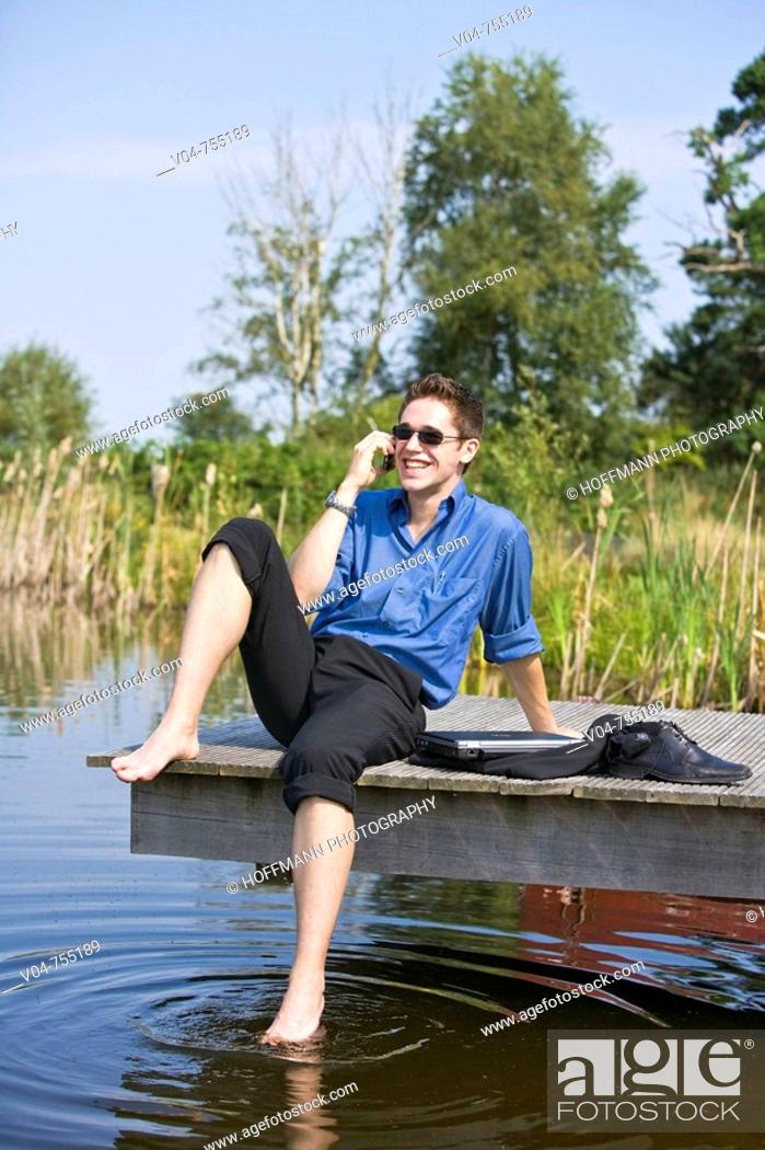 Stock Photo: Young business man using his cell phone at a pond.