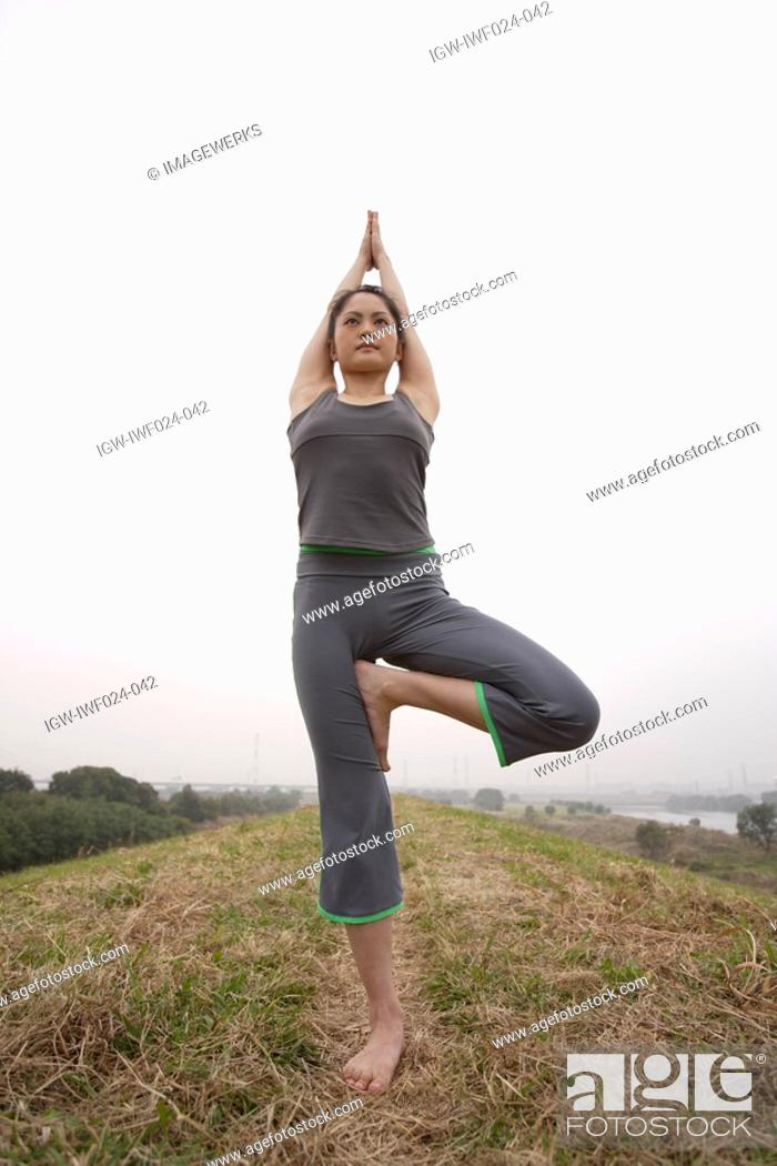 Stock Photo: Low angle view of a woman with tree position.