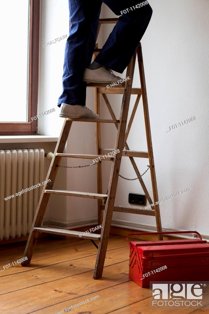 Stock Photo: A man standing on a ladder, low section.