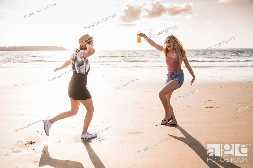 Stock Photo: Two girlfriends having fun, running and jumping on the beach.