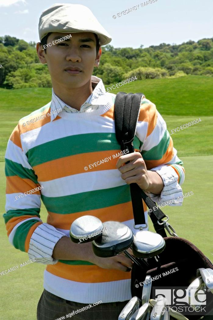 Stock Photo: Portrait of a young man carrying a golf bag.