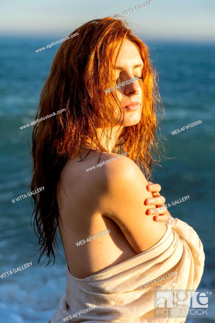 Stock Photo: Portrait of redheaded young woman with nose piercing in front of the sea.
