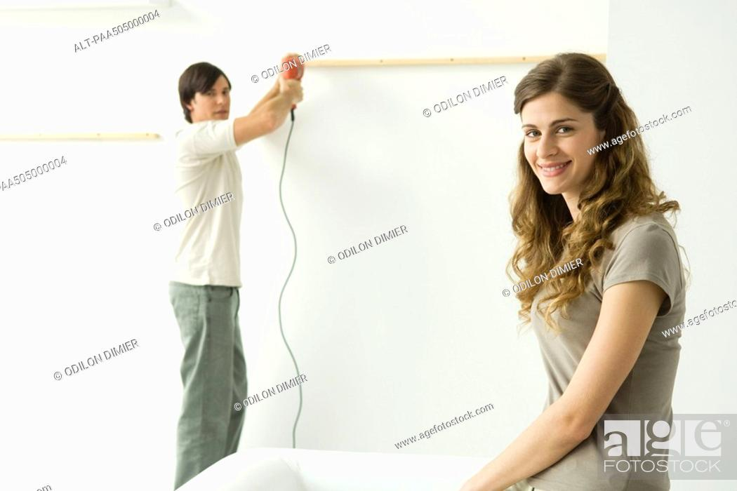 Stock Photo: Man attaching thin piece of wood to wall, woman in foreground smiling at camera.