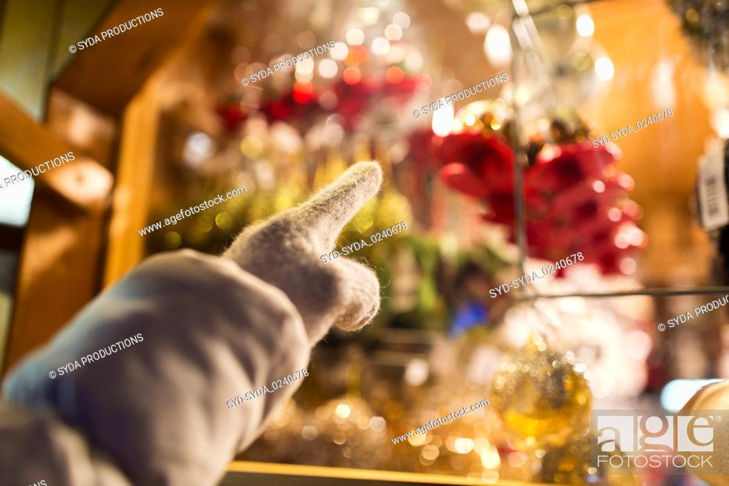 Stock Photo: hand pointing at christmas toys behind shop window.