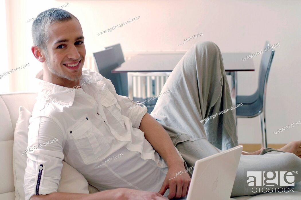 Stock Photo: Young man using laptop on couch.
