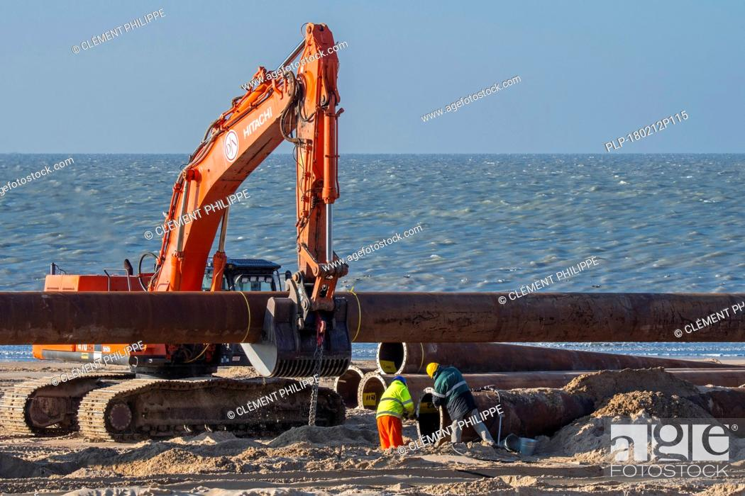 Stock Photo: Dredging workers connecting pipes of pipeline during sand replenishment / beach nourishment works along the Belgian coast at Ostend, Belgium.