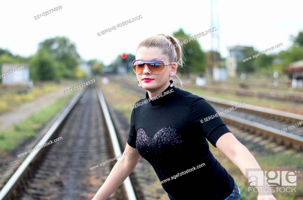 Stock Photo: the beautiful woman wears sunglasses on rails, a subject beautiful women and railway roads.