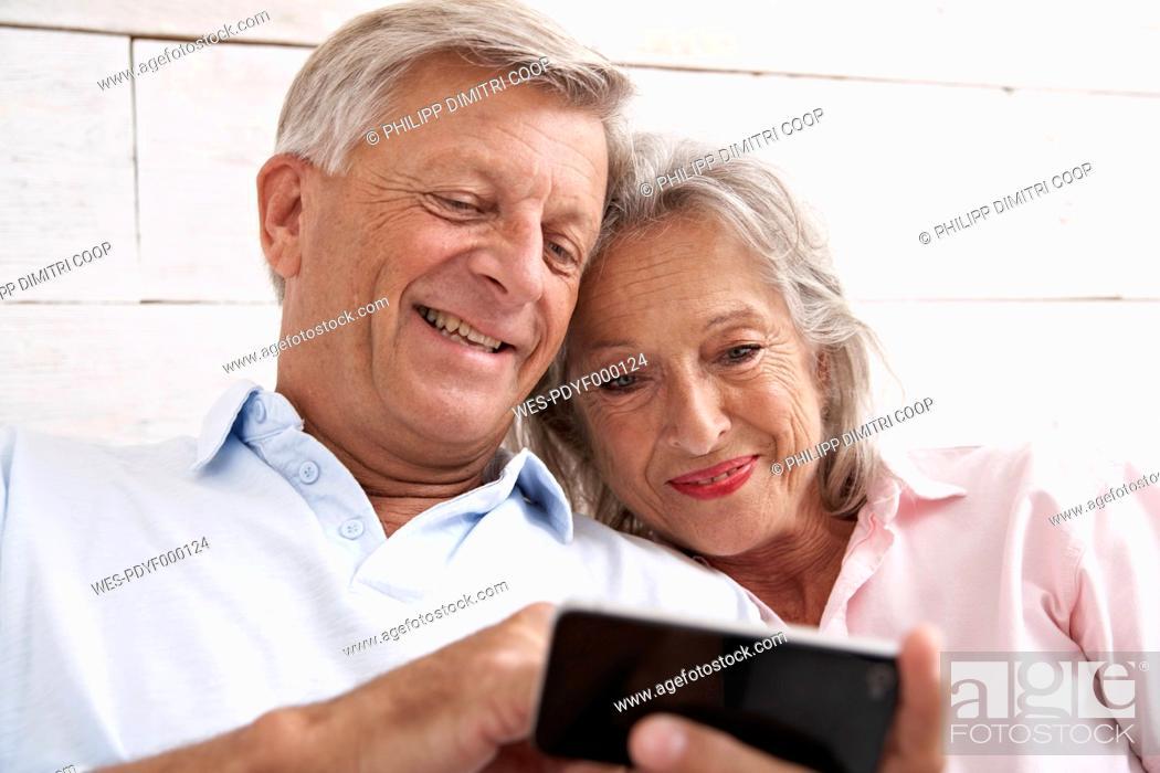 Stock Photo: Spain, Senior couple using mobile phone, smiling.