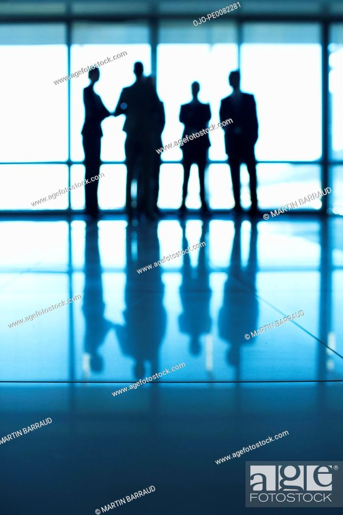 Stock Photo: Silhouette of business people standing at lobby window.