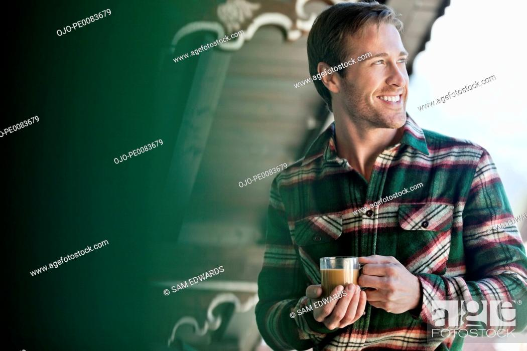 Stock Photo: Smiling man drinking coffee on cabin porch.