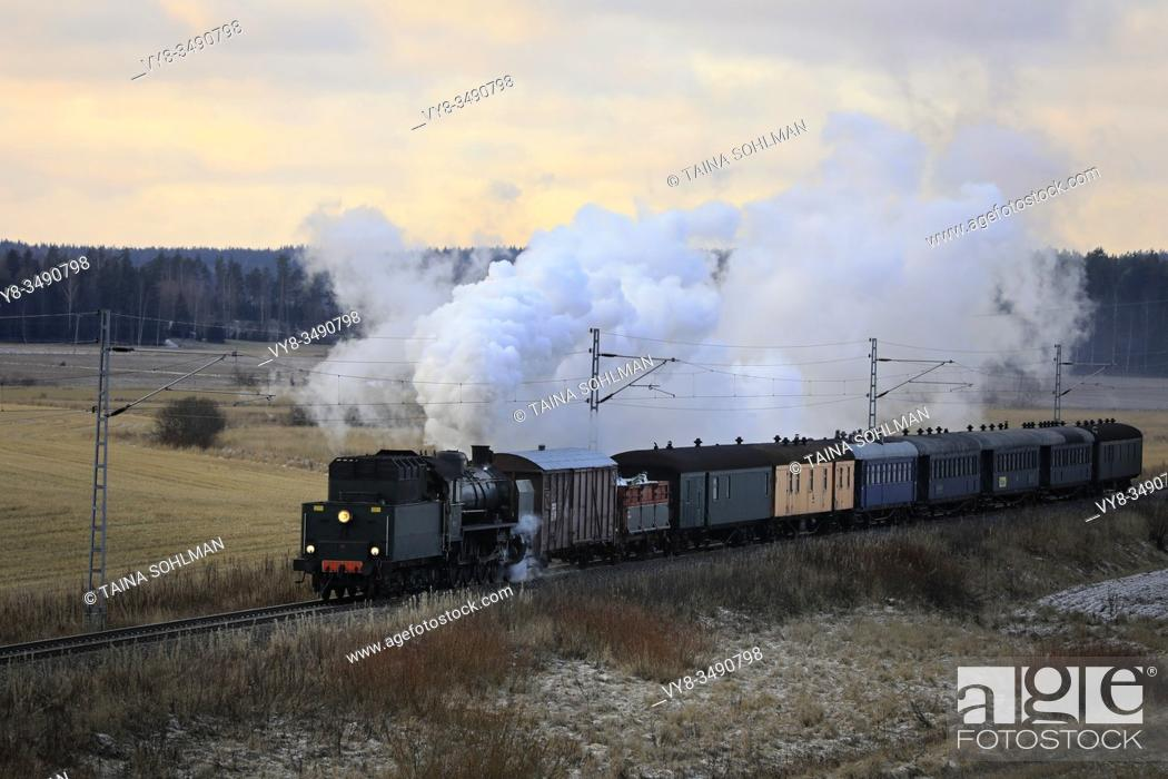 Stock Photo: VR Hr1 Class steam locomotive Ukko-Pekka 1009 pulling carriages on a winter morning through rural scenery in Hajala, Salo, Finland. December 27, 2019.
