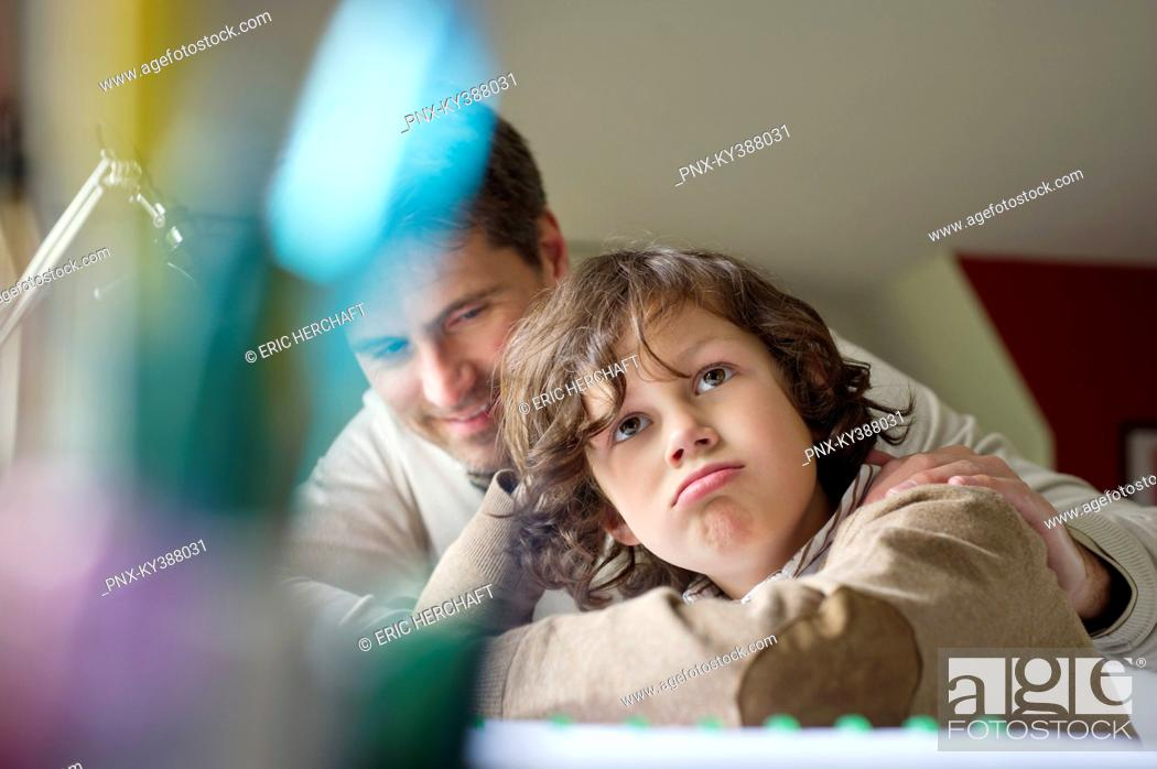 Stock Photo: Boy thinking while studying with his father at home.