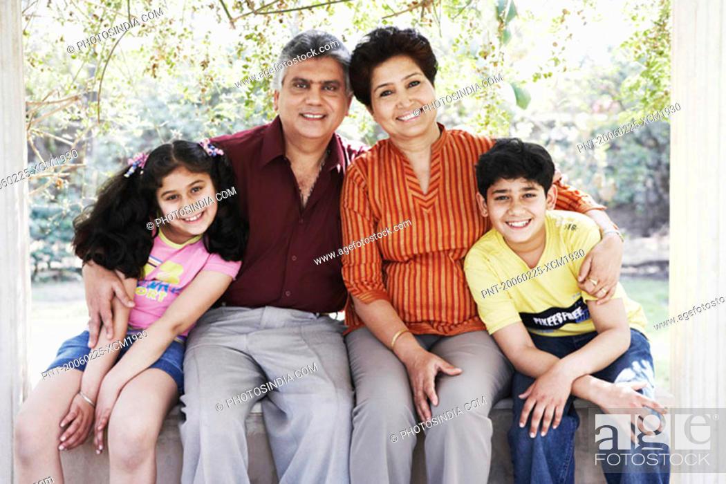 Stock Photo: Grandparent sitting with their two grandchildren.