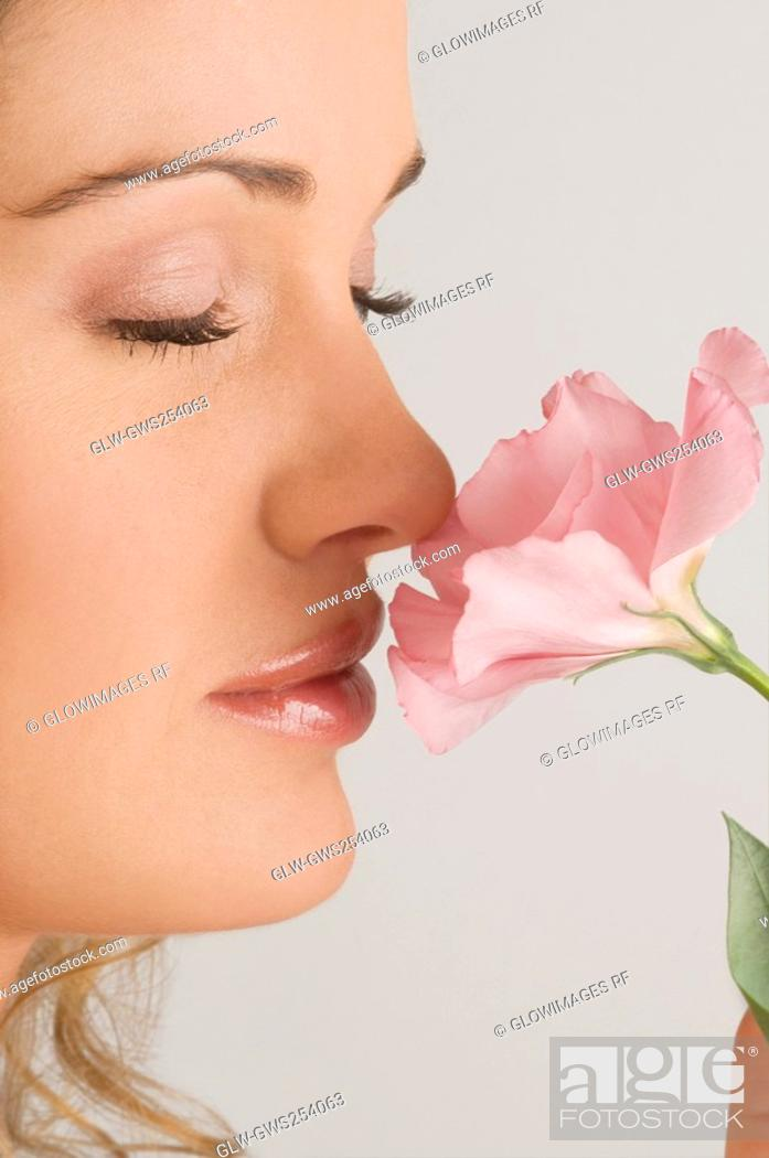 Stock Photo: Close-up of a young woman smelling a flower.