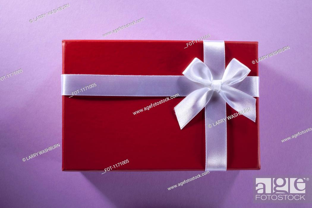 Stock Photo: A gift wrapped in red paper and white ribbon and bow.