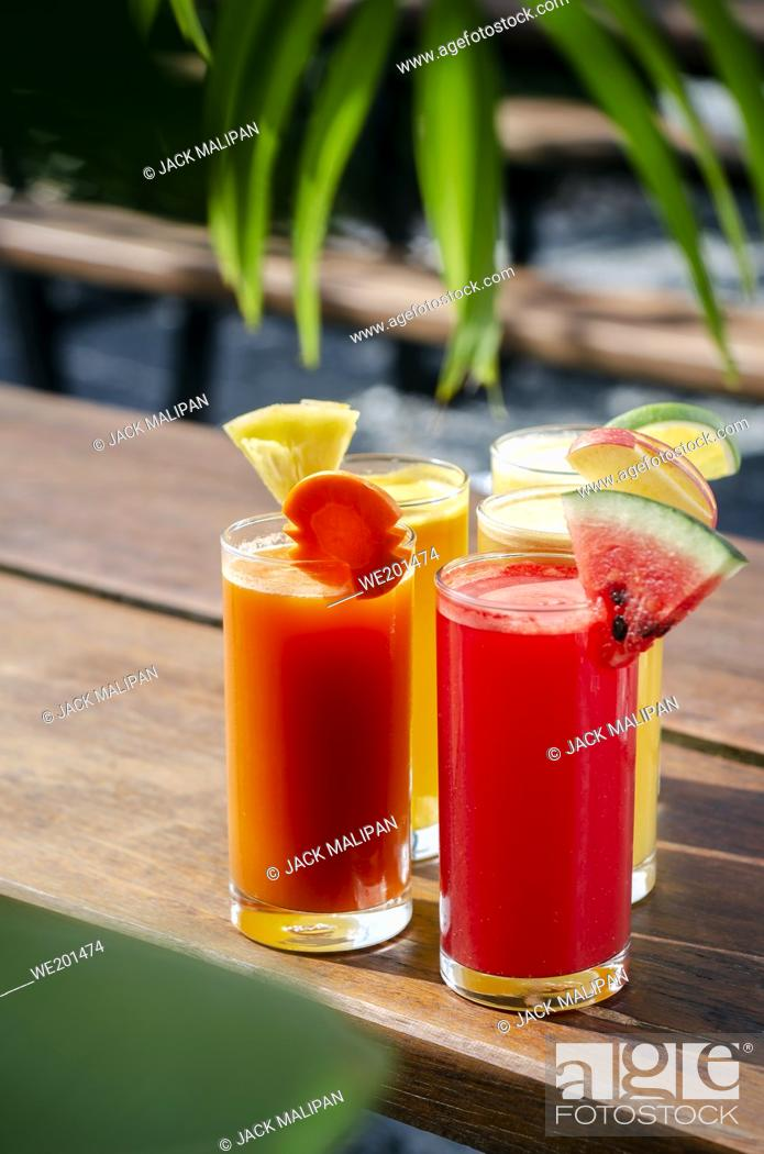 Stock Photo: mixed fresh organic fruit juice glasses selection on sunny garden table.