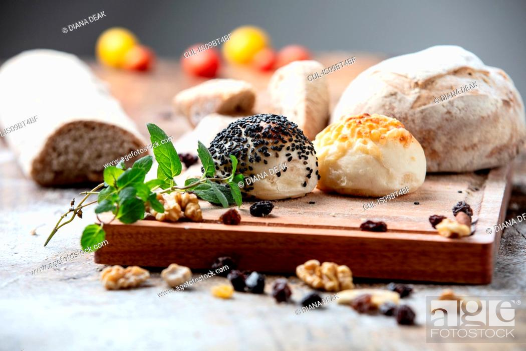 Imagen: Seeded bread rolls and rustic loaves on chopping board, still life.