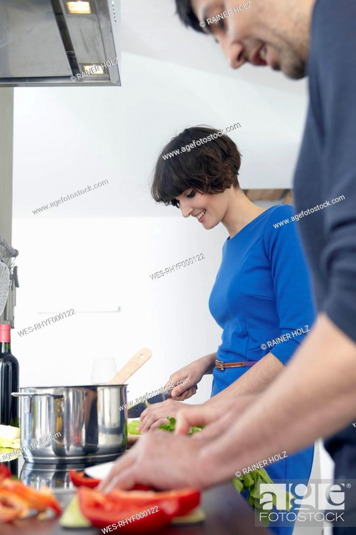 Stock Photo: Germany, Cologne, Man and woman cooking together in kitchen.