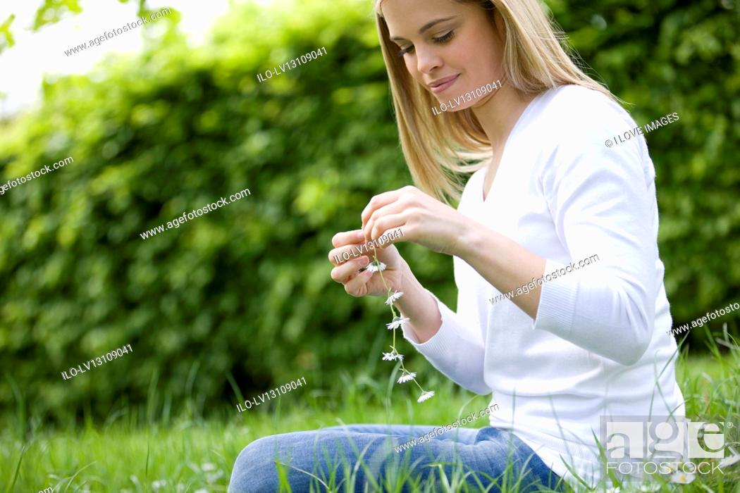 Stock Photo: A young woman sitting on the grass, holding a daisy chain.