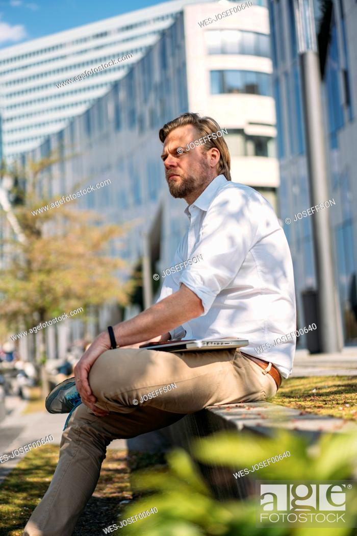 Stock Photo: Businessman having a break in the city sitting on a wall.