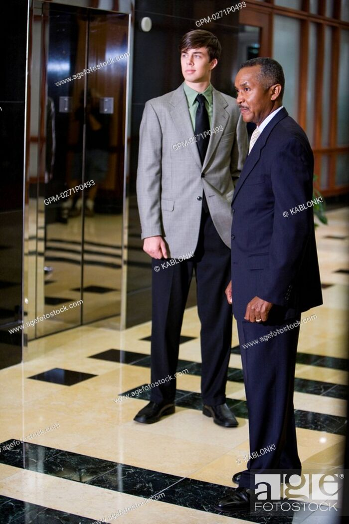 Imagen: Mature African American businessman with young colleague waiting for elevator in office building lobby.