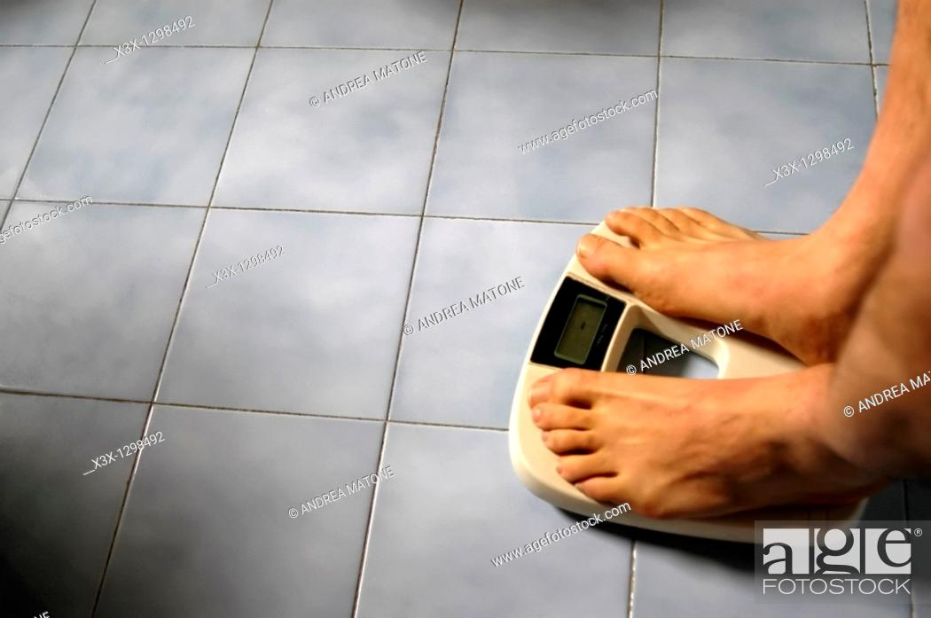 Stock Photo: Man standing on a bathroom weight scale.