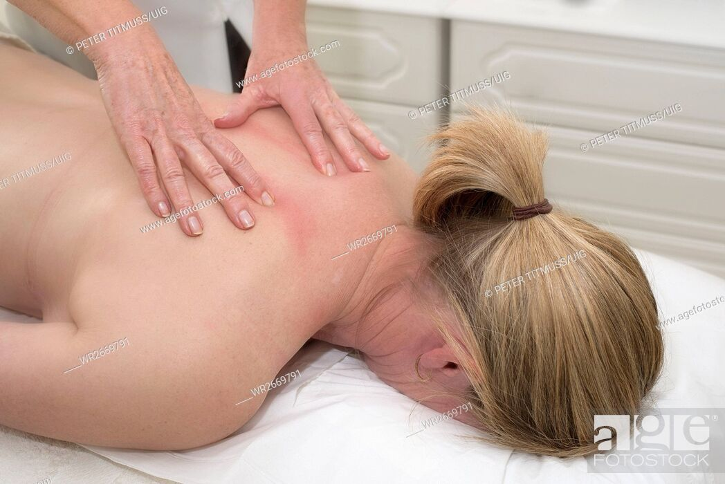 Stock Photo: Masseuse giving a massage to a female client.