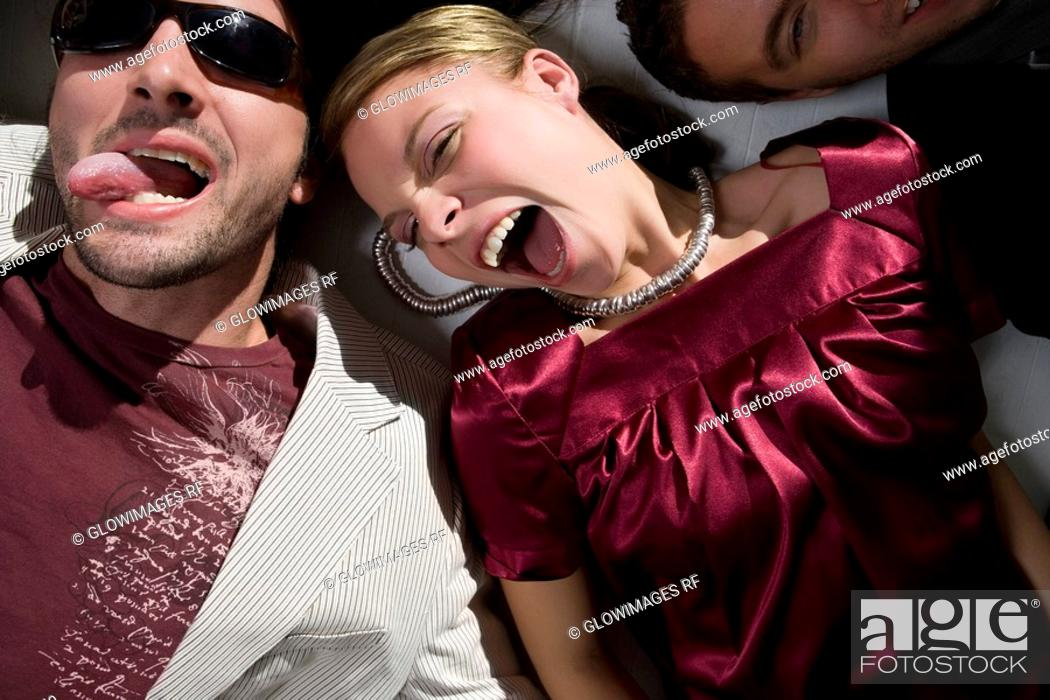 Stock Photo: High angle view of a young woman lying down with a young man sticking his tongue out.