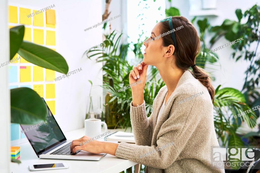 Stock Photo: Young woman with laptop on desk looking at adhesive notes on the wall.