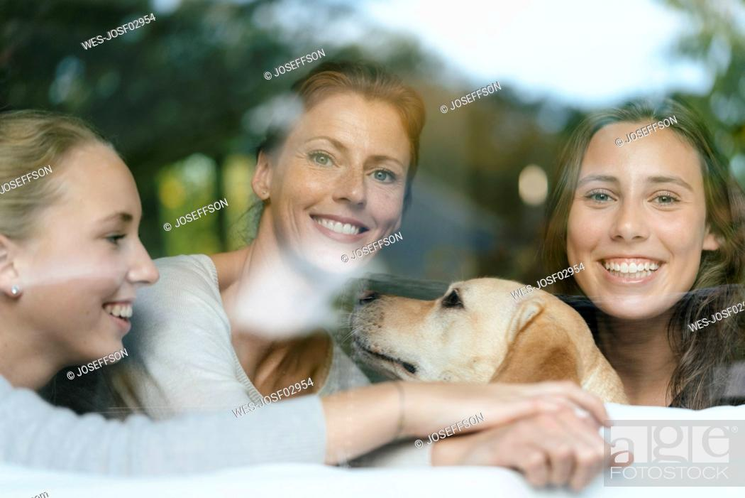 Imagen: Portrait of happy mother with two teenage girls and dog behind windowpane.