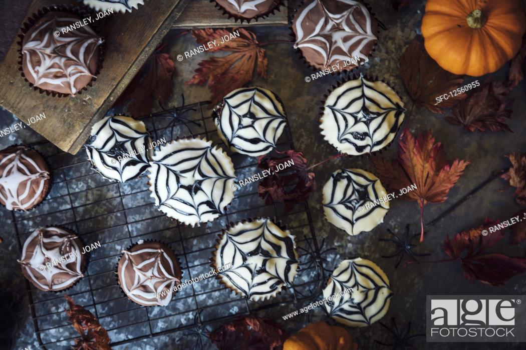 Stock Photo: Cobweb cakes for Halloween with mini pumpkins.