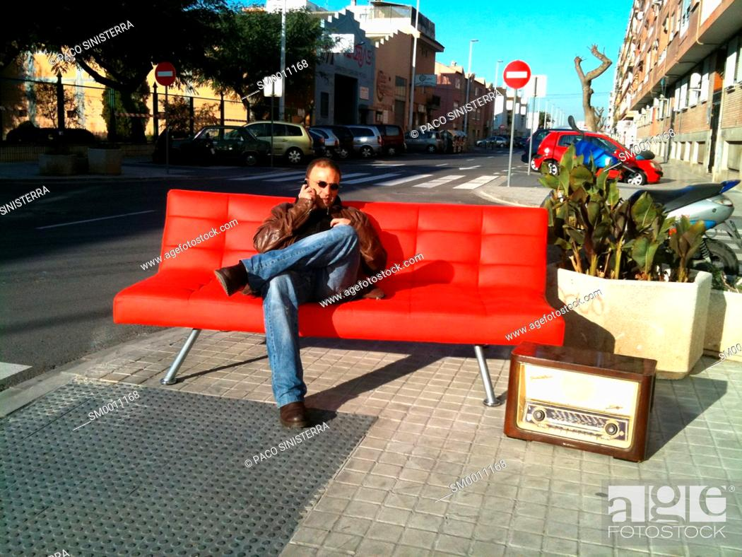 Stock Photo: Man on the phone on a couch in the street, Valencia, Spain.