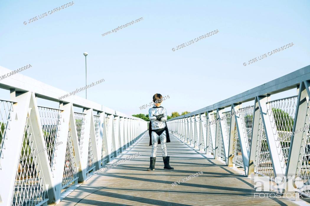 Stock Photo: Portrait of boy disguised as superhero standing on a footbridge.