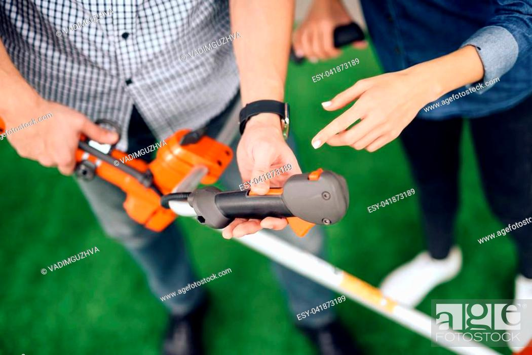 A Young Couple Came To The Garden Tools Store To Buy Equipment For
