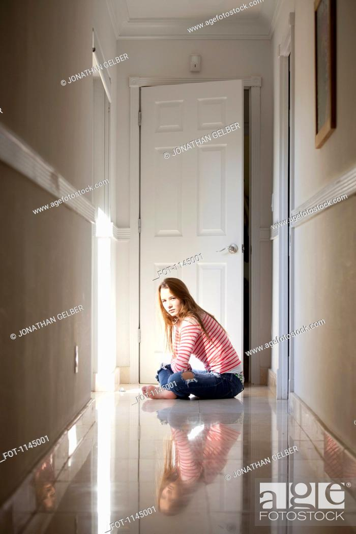 Stock Photo: Girl sitting cross-legged in hallway.