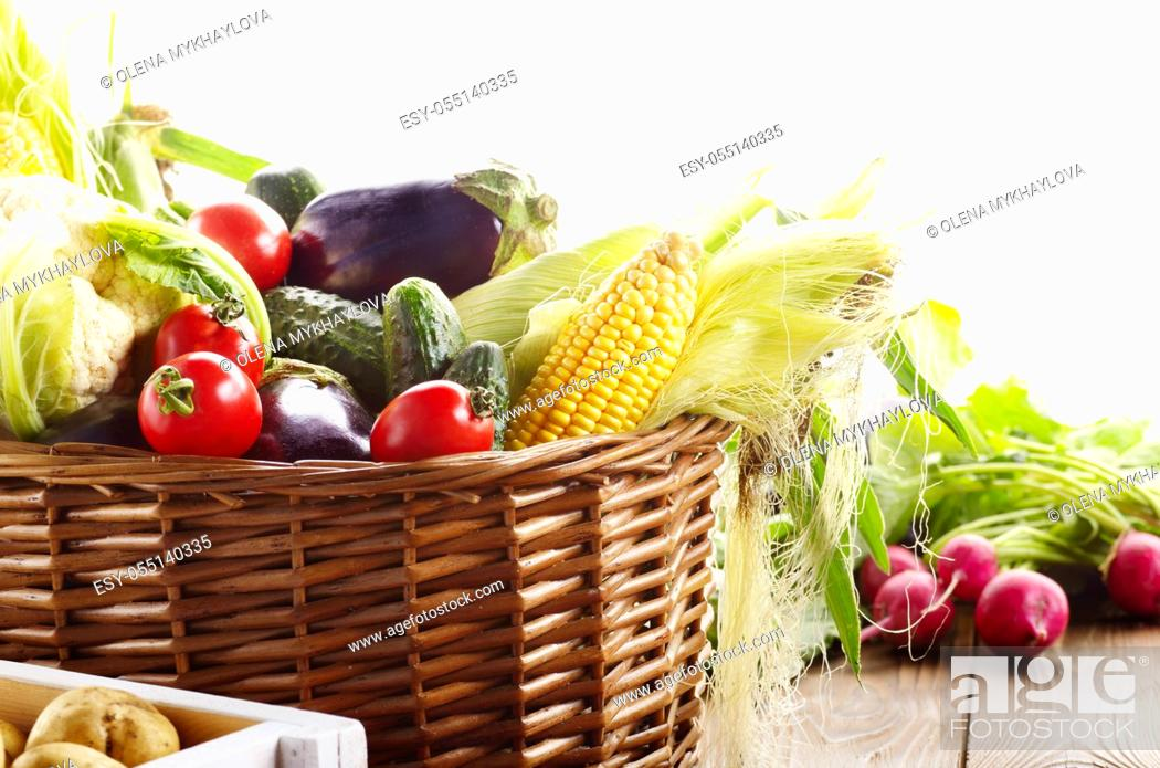 Stock Photo: Basket of Organic vegetable food ingredients and crate of potatoes on white background.
