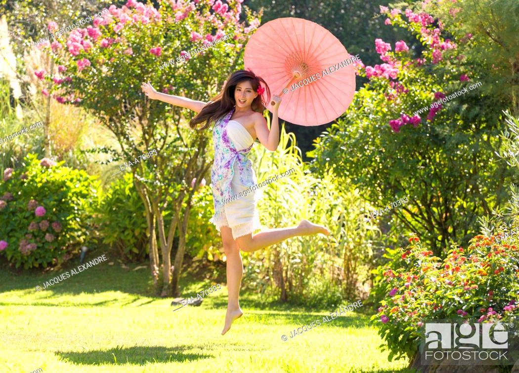 Imagen: woman dancing in park with umbrella.