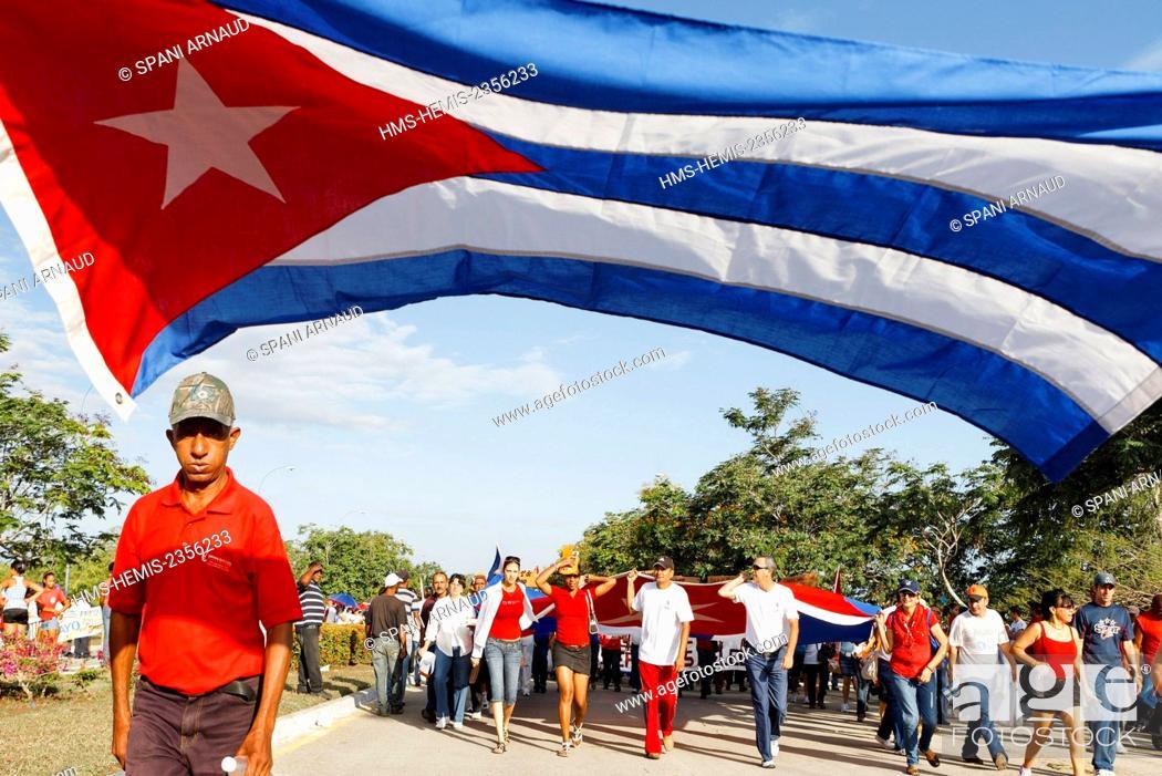 Stock Photo: Cuba, Villa Clara, Santa Clara, Huge Cuban flag carried by supporters.