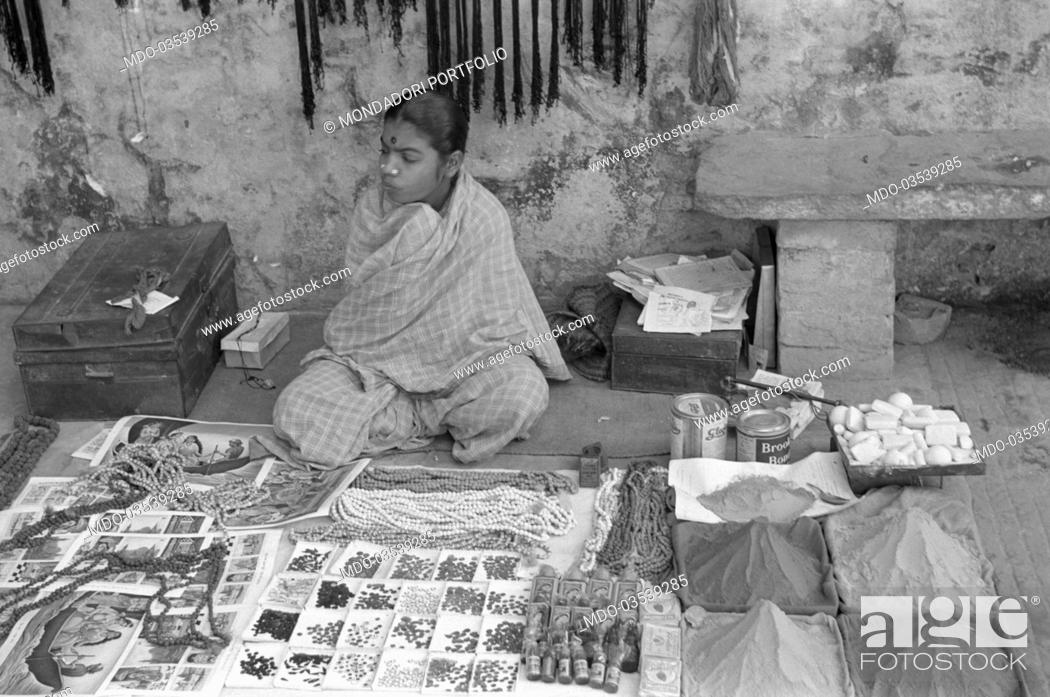 Stock Photo: A young street vendor displaying her goods on the street. Varanasi, 1965.