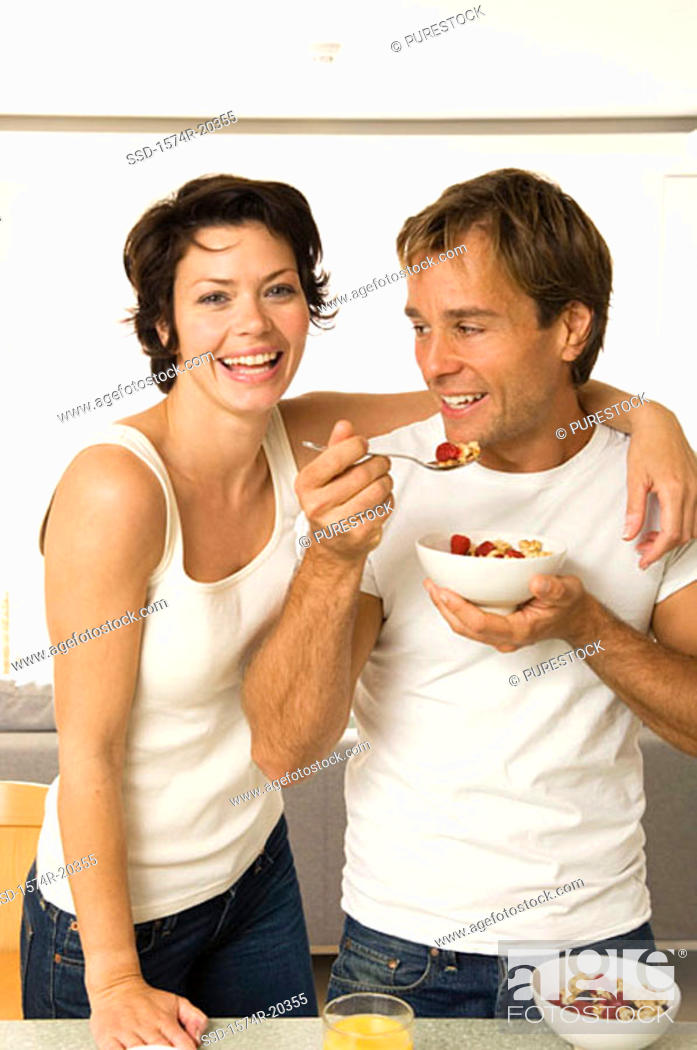 Stock Photo: Portrait of a young woman smiling with a young man eating fruit salad beside her.