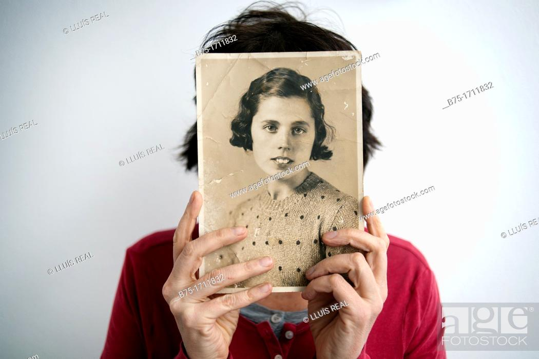 Stock Photo: Young woman with old picture in her hands, covering her face.