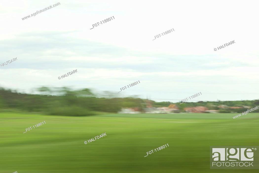 Stock Photo: A distant village in blurred motion viewed from moving train.