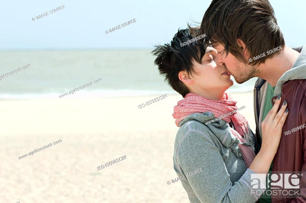 Stock Photo: Young couple kissing on a beach.