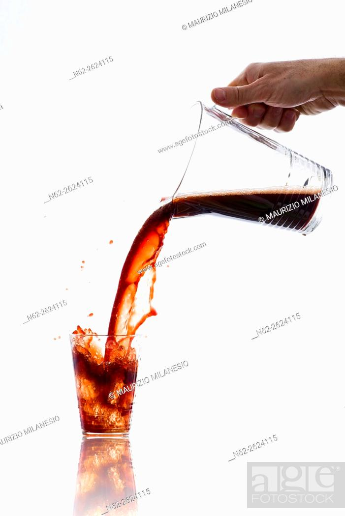 Stock Photo: Drink, vigorously poured from a carafe, overflowing splashing from a glass, on a white background.