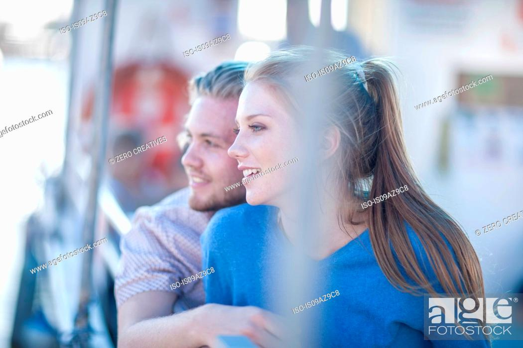 Stock Photo: Young tourist couple looking out on boat trip, Cape Town, South Africa.