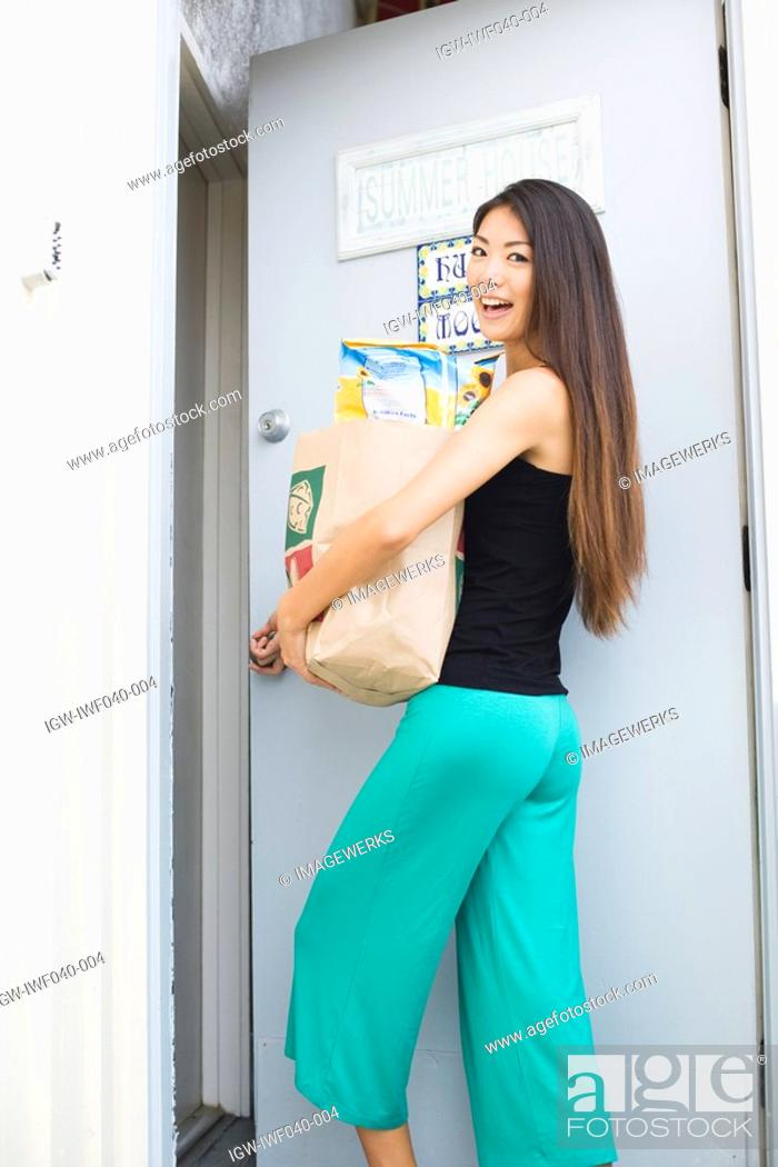 Stock Photo: A young woman holding paper bag.