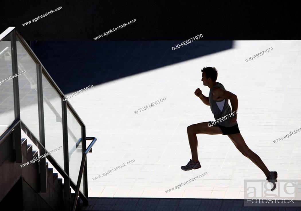 Stock Photo: Man running towards urban staircase.