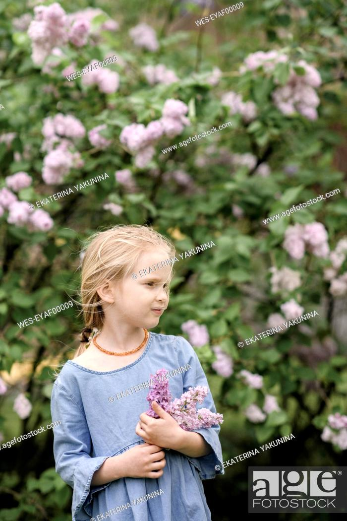 Stock Photo: Portrait of smiling girl with lilac blossoms.